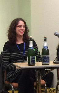 A woman seated behind a table with two bottles of champagne at a book launch